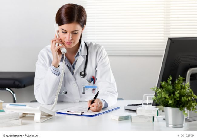 Female doctor at desk with telephone
