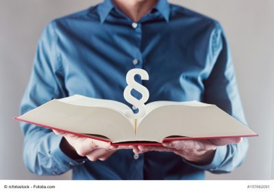young man holding book with paragraph sign - law concept image