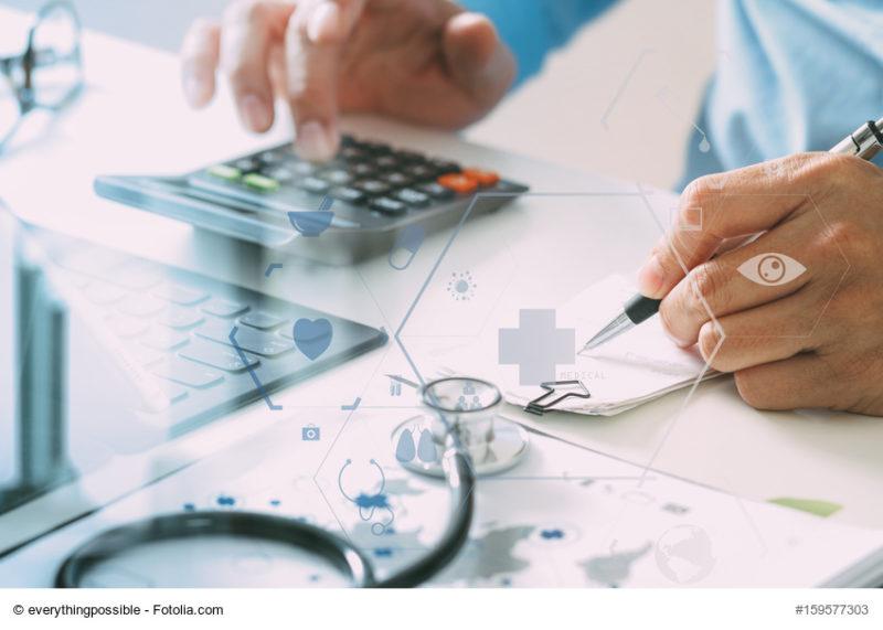 Ein Arzt macht mit einem taschenrechner und einem Notizblock eine Rechnung