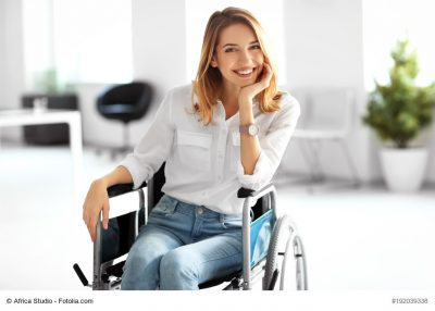 Young woman in wheelchair at workplace
