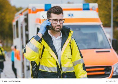 Medic talking to headquarter via radio in front of ambulance