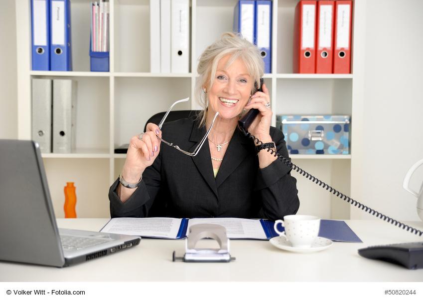Attraktive ältere Geschäftsfrau telefoniert im Büro