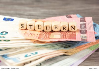 Geldscheine auf denen Würfel das Wort Steuern bilden