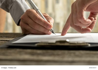 Closeup of businessman showing his new business partner where to sign an agreement or contract with fountain pen on rustic wooden desk.