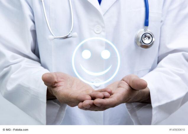 Arzt, der einen Smiley in Händen hält