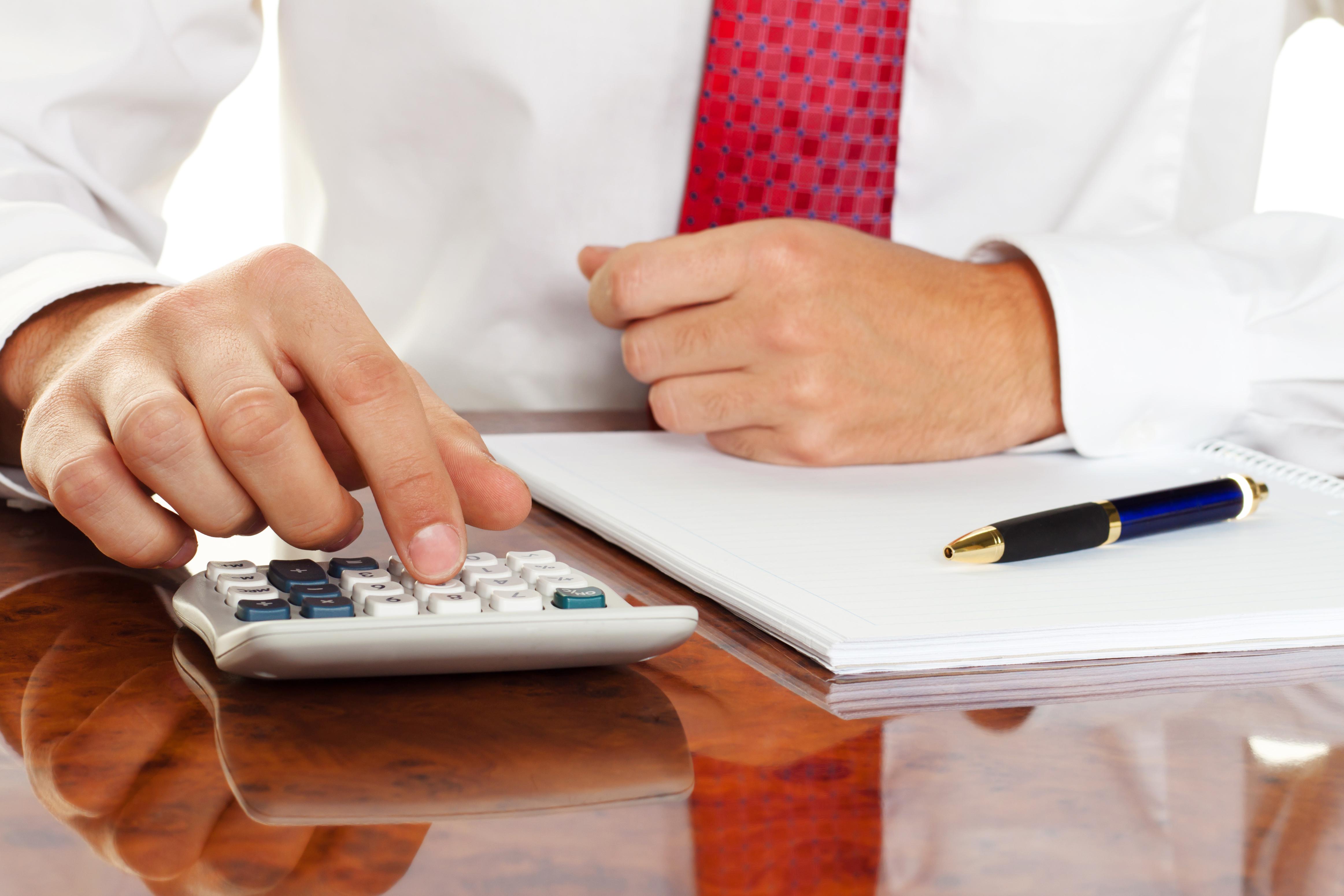 Geschäftsmann mit Taschenrechner. Berechnung von Kosten, Einnahmen, Bilanz