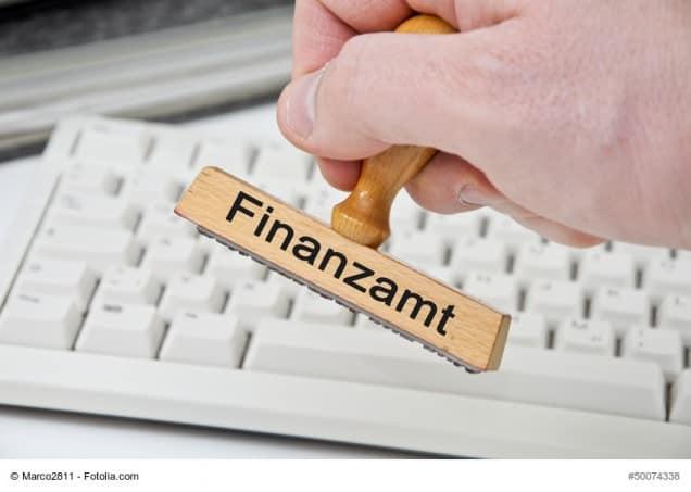 Ein Stempel, den ein Finanzbeamter in der Hand hält.