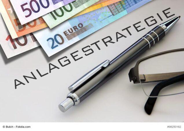 Papier mit der Aufschrift Anlagestrategie, Kugelschreiber, Geldscheine