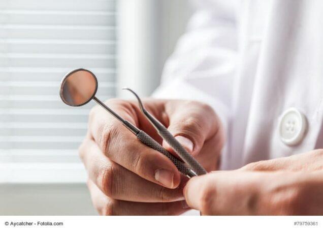 Zahnarzt, der medizinisches Besteck in Händen hält