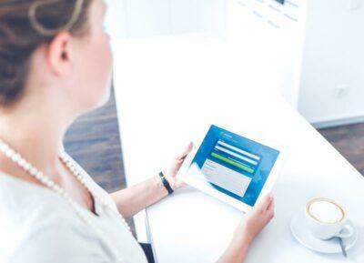 Frau schaut auf ein Tablet, auf dem die jameda-Seite angezeigt wird