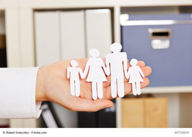 Familie als Silhouette aus Papier auf der Hand einer Frau
