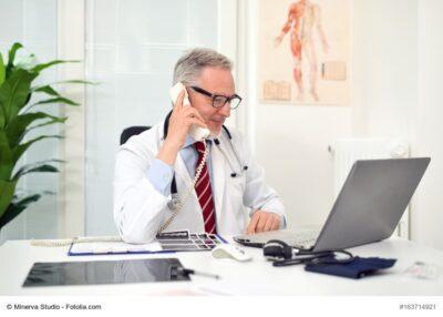 Arzt am Telefon blickt in den PC