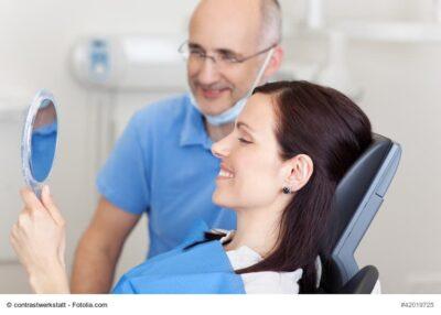 zufriedene Frau beim Zahnarzt schaut in den Spiegel