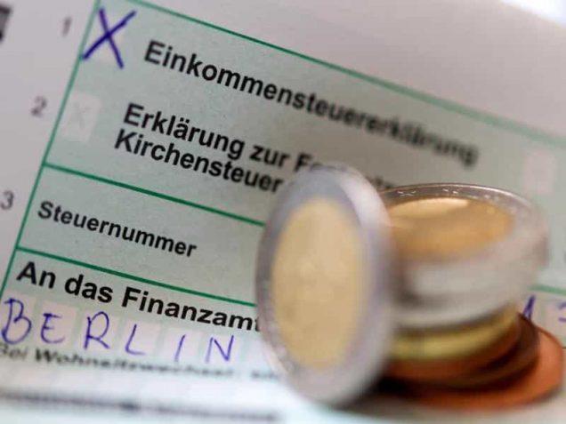 Formular für die Einkommensteuererklärung und Münzen