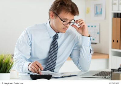 Portrait of office worker adjusting his glasses