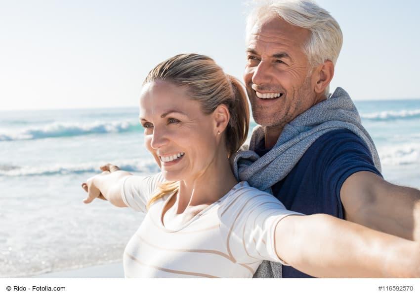Älterer Mann und ältere Frau mit offenen Armen am Meer