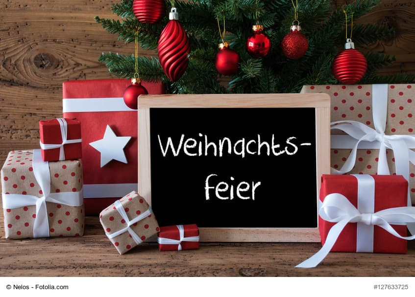 Chalkboard With German Text Weihnachtsfeier Means Christmas Party. Colorful Christmas Card For Seasons Greetings. Christmas Tree With Red Balls. Gifts Or Presents In The Front Of Wooden Background.