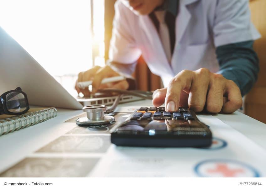 Arzt mit Taschenrechner und Stethoskop