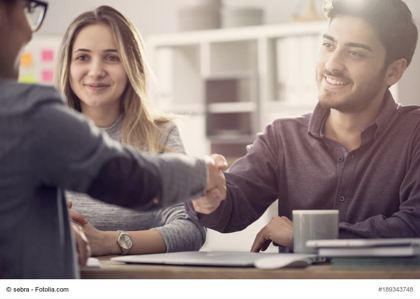 Junges Paar im Gespräch mit einem Bankberater