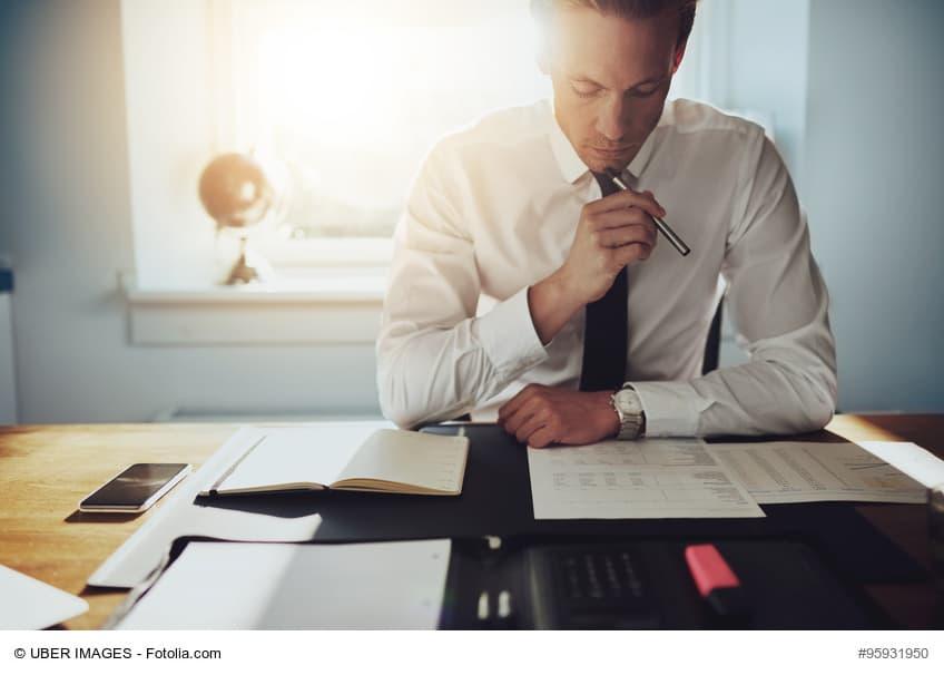 Mann sitzt am Schreibtisch und beugt sich über Unterlagen