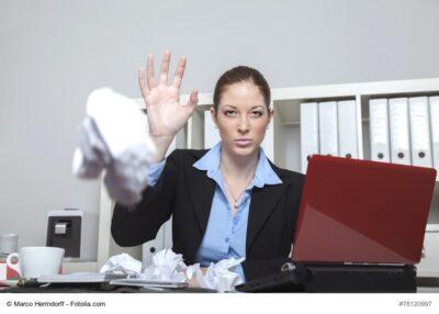 Frau im Büro wirft mit Papierball