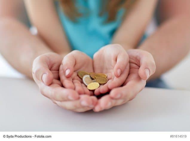 Vater hält schützend die Hände um die Hände seines Kindes, das Geld in den Händen hält