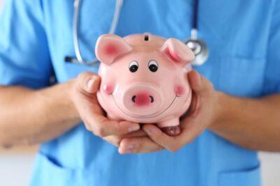 Arzt hält Sparschwein in der Hand