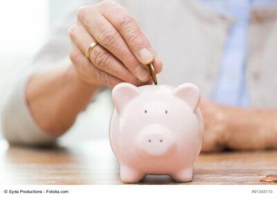 Frau steckt Münze in Sparschwein