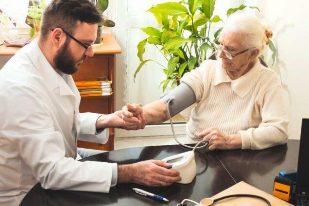 Arzt bei einem Patienten im Pflegeheim