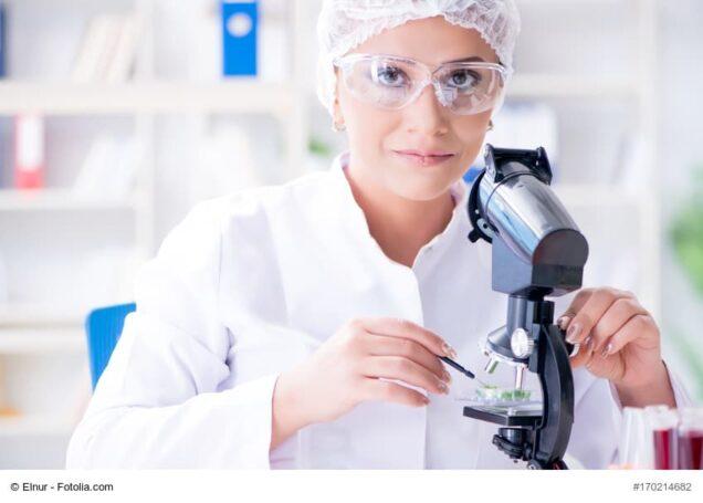 Frau sitzt in einem Labor am Mikroskop