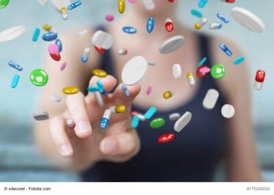 Frau tippt mit dem Finger auf Tabletten