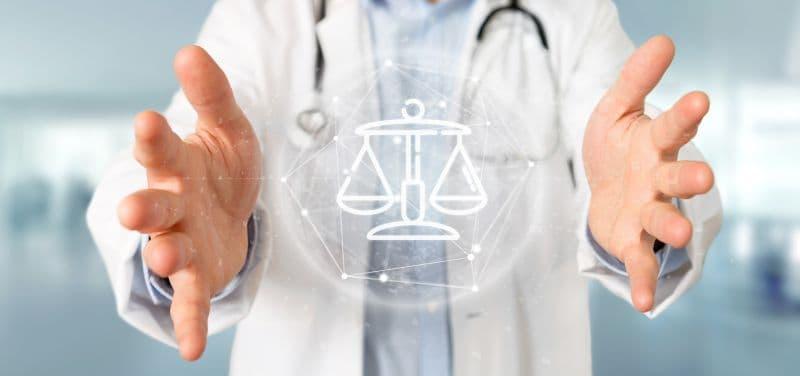 Arzt umfasst eine Glaskugel mit einer Waage