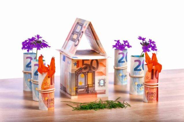Geldscheine, aus denen ein Haus mit Garten gefaltet wurde
