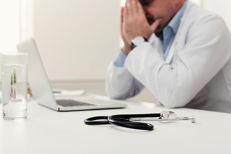 Arzt sitzt betroffen am Schreibtsich und shclägt die Hände vors Gesicht