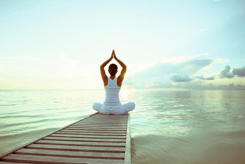 Frau auf einem Steg am See macht Yoga