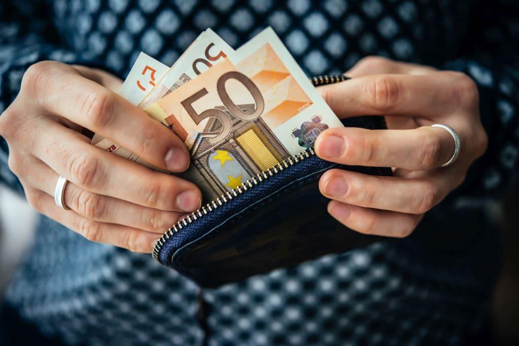 Mann holt Geld aus dem Geldbeutel