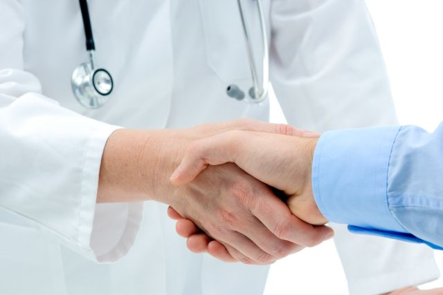 Doctor shakes hands with a patient isolated on white background