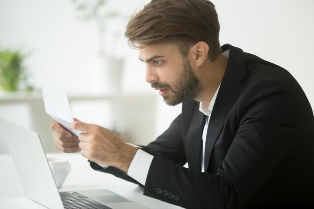 Amazed surprised businessman in suit shocked by reading mail let