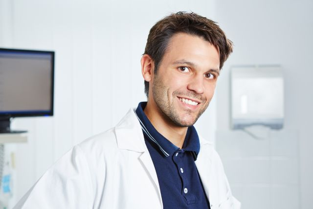 Portrait von einem lächelnden Arzt im Kittel in seiner Praxis