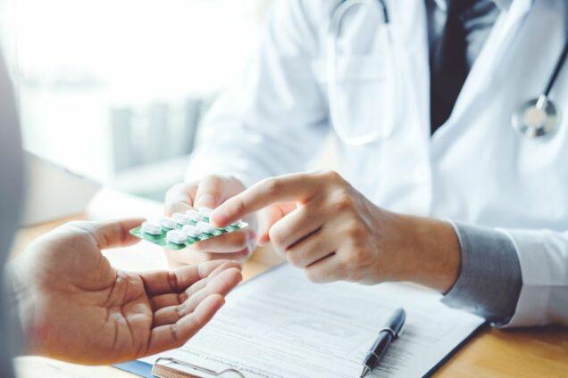 Ärztin gibt Patient Tabletten