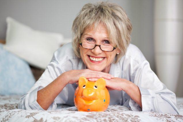 ältere Frau stützt Hände auf Sparschwein