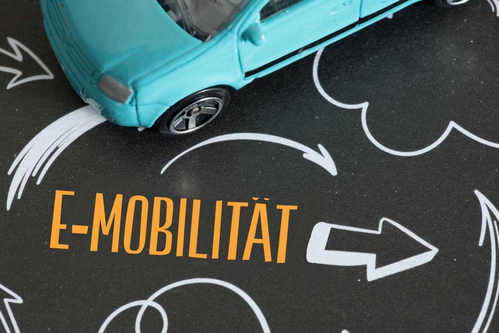 Ein Auto und ein Pfeil der in Richtung e-Mobilität zeigt