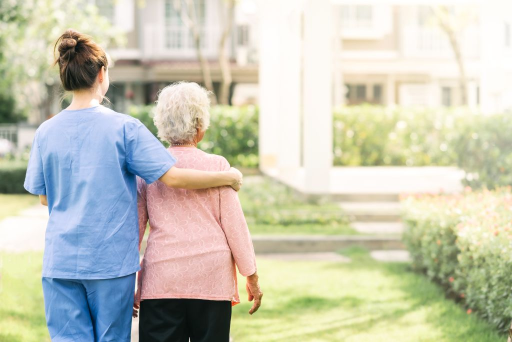nurse caregiver support walking with elderly woman outdoor