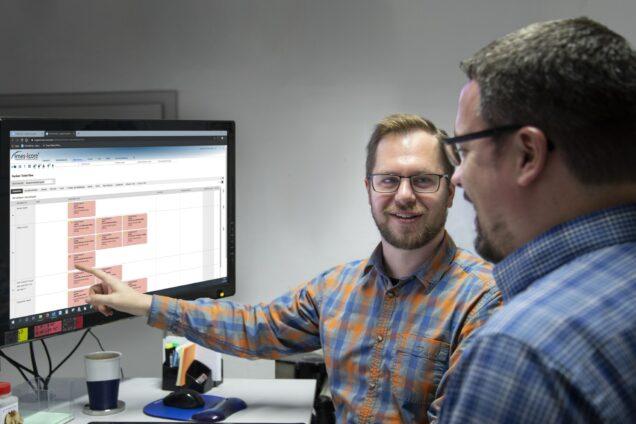 Zwei IT-Experten schauen auf einen Bildschirm