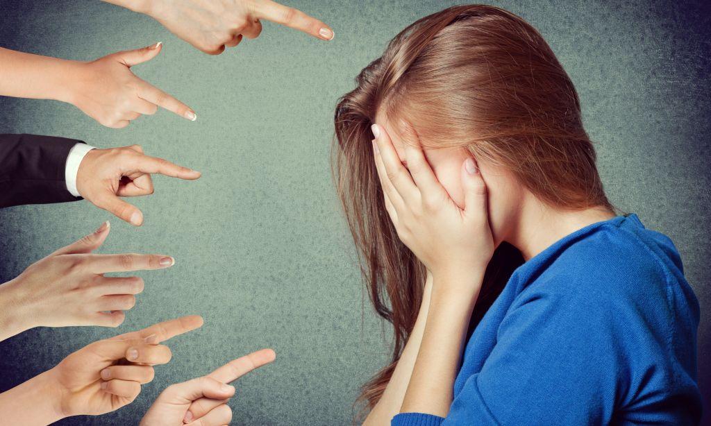 Finger zeigen auf Frau, die Hände vors Gesicht schlägt