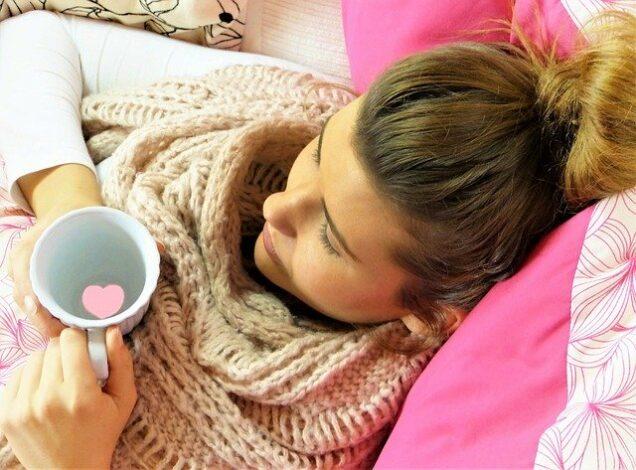 Frau liegt krank im Bett mit einer Tasse in der Hand
