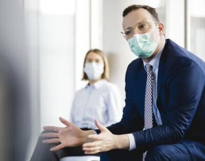 Jens Spahn mit Mund-Nasen-Schutz im Gespräch