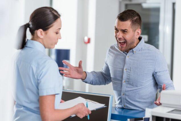 Patient diskutiert mit Arzthelferin