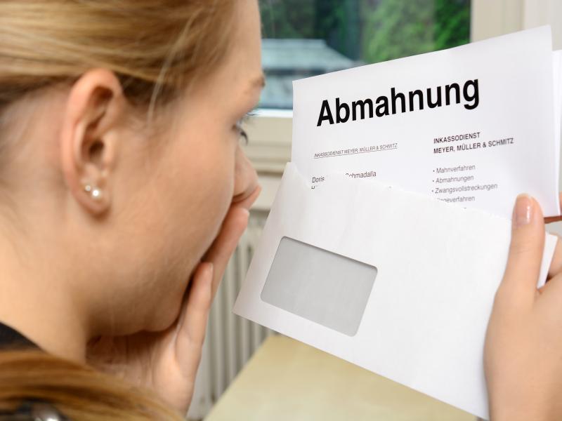 Frau schaut auf Brief mit der Aufschrift Abmahnung