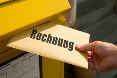hand schiebt Rechnung in einen Briefkasten
